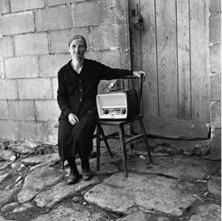Señora con el receptor de radio adquirido con el dinero enviado por su hijo, emigrante en América