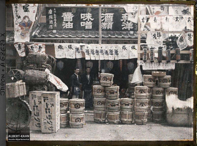 Epiciers à l'entrée de leur boutique, devant laquelle sont exposés des fûts de bière, de «miso» (pâte de haricots de soja fermentée), de saké et du charbon de bois, Tôkyô, Japon, 1926-1927, (Autochrome, 9 x 12 cm), Roger Dumas, Département des Hauts-de-Seine, musée Albert-Kahn, Archives de la Planète, A 68 627 X