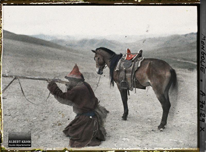 Chasseur mongol descendu de cheval faisant une démonstration du maniement du fusil à pierre, Aux environs d'Ourga, Mongolie, 20 juillet 1913, (Autochrome, 9 x 12 cm), Stéphane Passet, Département des Hauts-de-Seine, musée Albert-Kahn, Archives de la Planète, A 70 129 XS
